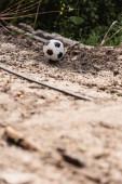 A focilabda szelektív fókusza a piszkos út talaján a városi utcában