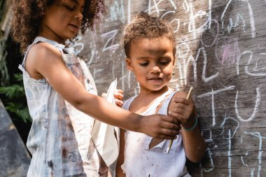 Selective focus of poor african american kids in torn clothes standing near chalkboard and holding pencil stock vector
