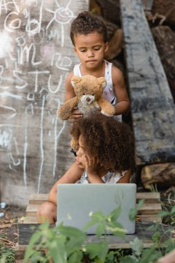 Selective focus of dirty african american kids with laptop and teddy bear on urban street stock vector