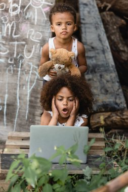Selective focus of shocked african american child looking at laptop near brother holding teddy bear on urban street stock vector