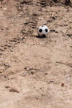 Selective focus of soccer ball on ground on urban street stock vector