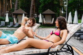cheerful woman in sunglasses looking at shirtless man talking and gesturing while lying on sunbed
