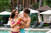 glückliches Paar, das Cocktails trinkt und sich am Swimmingpool anschaut
