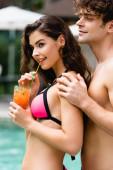 happy man touching girl drinking cocktail through straw
