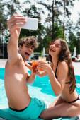 Selektiver Fokus von glücklichen Männern und Frauen mit Sonnenbrille, die Cocktails in der Hand halten und ein Selfie in der Nähe des Swimmingpools machen
