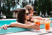 boldog pár napszemüvegben mosolyog alkohol koktélok közelében