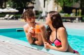 Fröhliches Paar klingelt bei Cocktails im Schwimmbad