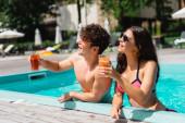 fröhliches Paar mit Sonnenbrille hält Cocktails im Swimmingpool