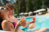 selective focus of cheerful girl in sunglasses holding cocktail near man in swimming pool