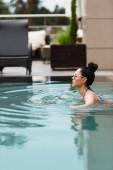 boční pohled na atraktivní dívku v slunečních brýlích plavání v bazénu
