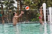 šťastný pár hrát volejbal s plážovým míčem v bazénu