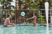 veselý pár hraje volejbal s plážovým míčem v bazénu