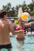 selektivní zaměření dívky a muže bez trička hrající volejbal s plážovým míčem v bazénu