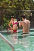 Fotografie Selektiver Fokus des hemdslosen Mannes, der ein Foto von sexy Mädchen im Badeanzug im Swimmingpool macht