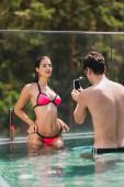 Fotografie muskulöser Mann fotografiert sexy Mädchen im Badeanzug im Schwimmbad