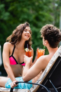 Happy woman in swimsuit looking at man while holding cocktail stock vector