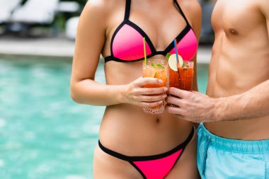 Cropped view of couple in swimwear holding glasses with cocktails stock vector
