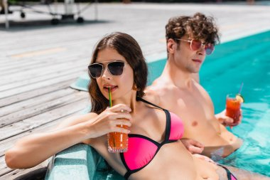 Selective focus of attractive woman in sunglasses holding cocktail near man in swimming pool stock vector