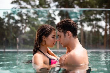 profile of couple with closed eyes in swimming pool