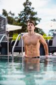 selektivní zaměření sexy a svalnatý muž při pohledu na kameru v bazénu