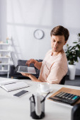 Selective focus of concentrated freelancer holding laptop and sitting near table with stationery at home, earning online concept
