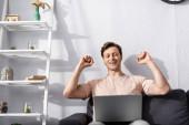 Selektivní zaměření veselý freelancer ukazující jo gesto při pohledu na notebook na gauči doma, vydělávat on-line koncept