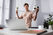 Selective focus of cheerful man holding football and money near laptop at home, concept of earning online