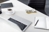 Szelektív fókusz dollár közelében laptop, notebook és csésze kávé az asztalon, kereső online koncepció