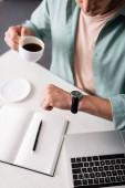 Vágott kilátás a szabadúszó ellenőrzése idő karóra, miközben iszik kávé közelében laptop és notebook, koncepció az időgazdálkodás