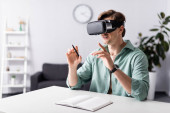 Smiling man in vr headset holding pen near open notebook on table