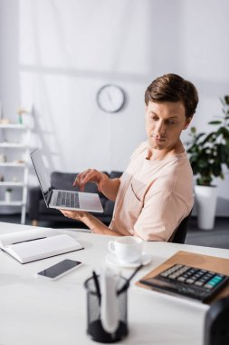 Selective focus of concentrated freelancer holding laptop and sitting near table with stationery at home, earning online concept stock vector