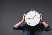 Photo Young man holding wall clock near head on grey background, concept of time management