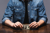 Cropped view of young man holding dollars at table isolated on grey