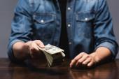 Oříznutý pohled na muže ukazujícího dolary u stolu izolovaného na šedi