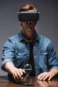 Selektivní zaměření člověka ve virtuální realitě sluchátka tahání ruku v ruce přesýpací hodiny na stole na šedém pozadí, koncept time managementu
