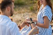 Selektiver Fokus eines bärtigen Mannes mit Flasche beim Einschenken von Rotwein in Glas in der Nähe einer glücklichen Frau