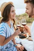 veselý pár cinkající sklenice s červeným vínem venku