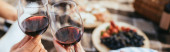 panoramic crop of couple clinking glasses with red wine