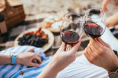 selective focus of man and woman clinking glasses with red wine