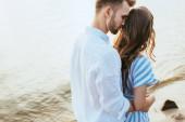vousatý muž objímání přítelkyně poblíž jezera