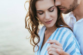 selective focus of bearded man holding hands with attractive girl