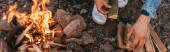 panoramische Vorstellung von einem Mann, der Holzstämme in der Nähe brennenden Feuers berührt