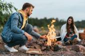 selektivní zaměření muže sedícího poblíž hořícího táboráku a dívky