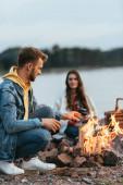 selektiver Fokus eines gutaussehenden Mannes, der neben Freundin sitzt und brennendes Lagerfeuer betrachtet