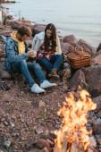 Selektiver Fokus des Paares auf Steinen in der Nähe von Lagerfeuer und See