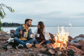 selective focus of couple holding cups and sitting on rocks near bonfire and lake