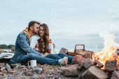 selective focus of happy man hugging attractive girl with cup near bonfire