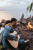selektivní zaměření vousatý muž hrající na akustickou kytaru poblíž přítelkyně, řeky a táboráku