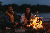 selektivní zaměření šťastného páru pečení marshmallows na tyčinky v blízkosti táboráku v noci