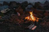 hořící táborák u kostkované přikrývky, proutěný koš, šálky a akustická kytara